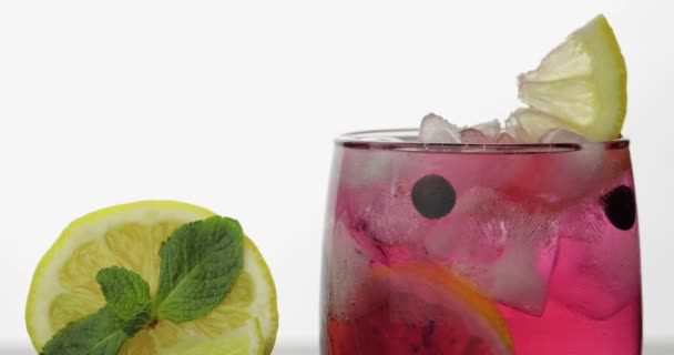 Minzblätter in einem Glas mit kaltem Getränk, Limette, Zitrone, Johannisbeeren, Eis hinzufügen
