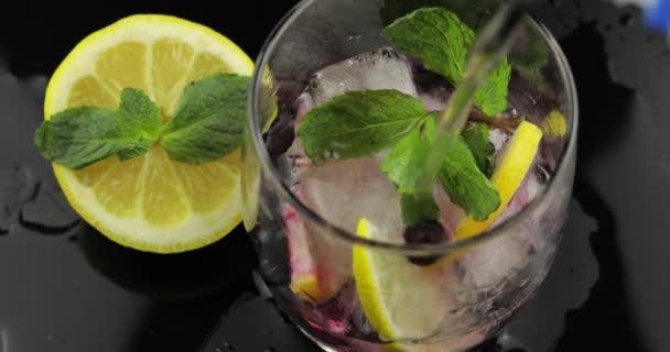Gießen Sie Wasser in ein Glas mit Blättern aus Minze, Limette, Zitrone, Johannisbeeren, Eiswürfeln