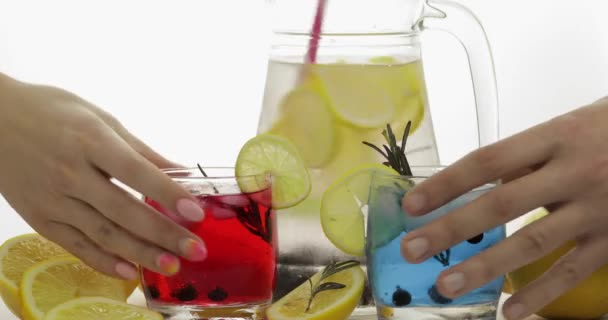 Woman and man hands takes refreshing soda red and blue cocktails with lemon