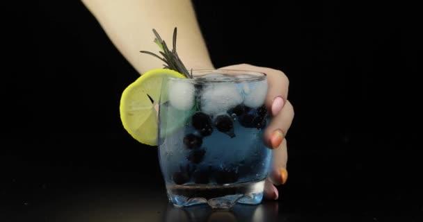 Frau Hand nimmt und legte erfrischende Limonade blauen Cocktails mit Zitrone