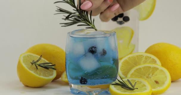 Hinzufügen rosmarinfarbener Zweig in einem Glas mit Sodalimonade blauem Cocktail