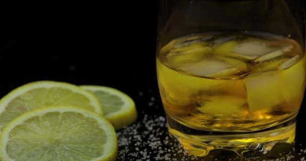 Whisky s ledem. Nalití whisky rum z láhve na černém pozadí