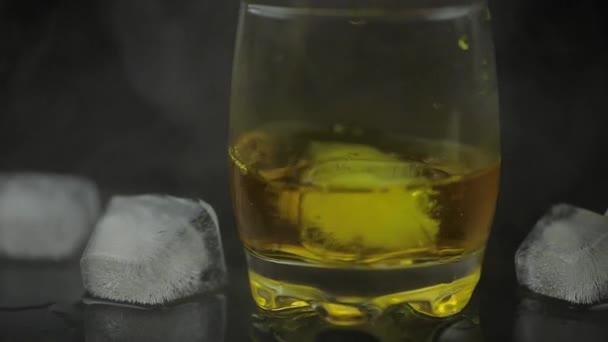 Whisky s ledem. Přidání kostky ledu na černé pozadí. Sklenice rumového alkoholu