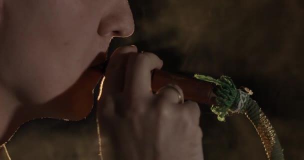 Csinos, fiatal ember dohányzás vízipipa. Vonzó Guy dohányzás ízesített dohány
