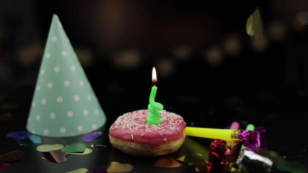 Party. rosa Donut und eine rote Festkerze darauf. Goldener Konfettiregen