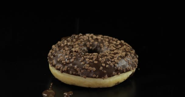 Delicious melted dark chocolate syrup pouring over a donut on black background