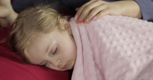 Junge Mutter kümmert sich um ihr kleines Mädchen, während es schläft. Mädchen auf dem Bett