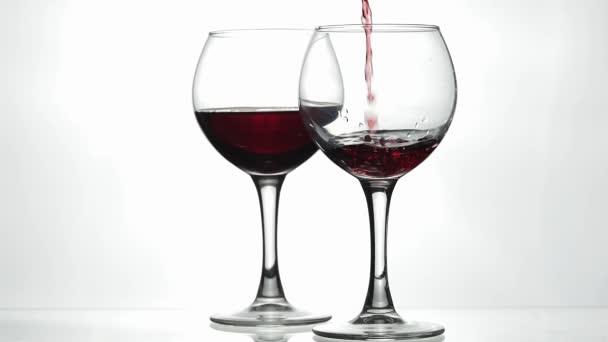 Rosenwein. Rotwein in Weinglas über weißem Hintergrund gießen. Zeitlupe