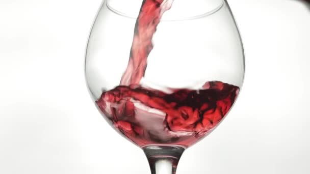 Rose wine. Red wine pour in wine glass over white background. Slow motion
