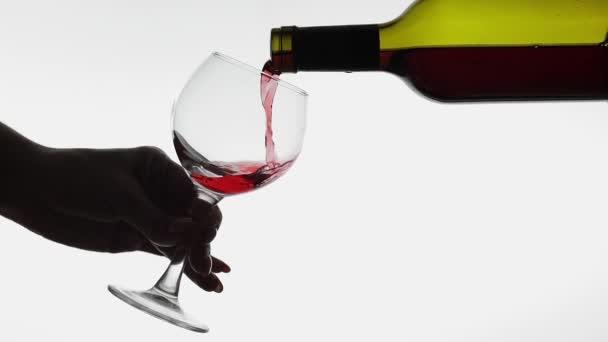 Rose bort. Vörösbor pour borpohár fehér háttér előtt. Lassított mozgás
