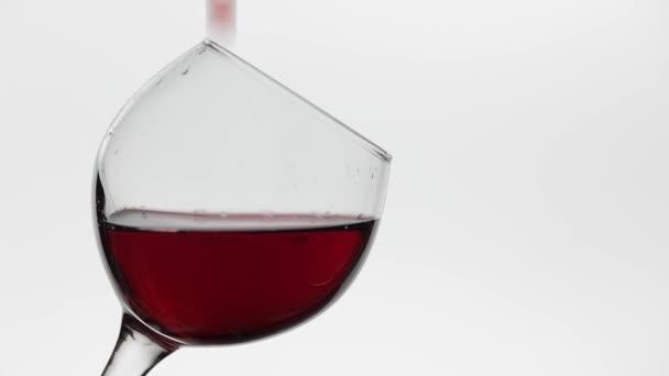 Közelről egy csepp üveg alá a vörösbor. Rózsaszibor fehér alapon
