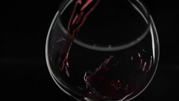 Rose bort. Fekete hátterű borpohár, vörösbor. Lassított mozgás