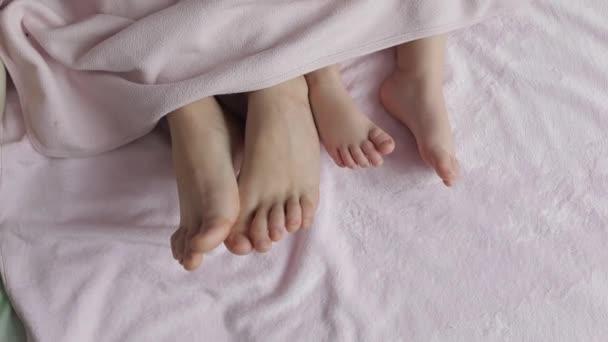 zwei Beinpaare der Familie im Bett unter der Decke - Mutter und Baby
