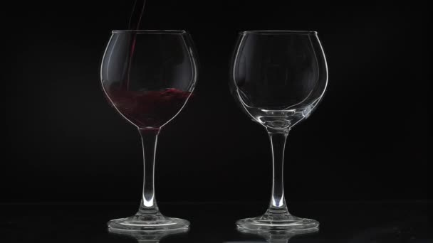 Růžové víno. Červené víno nalije dvě skleničky na černé pozadí. Silueta