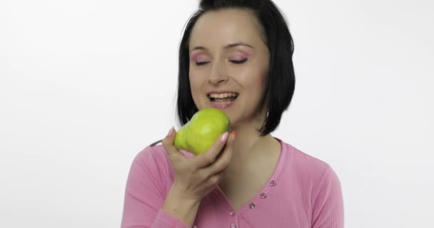 Woman eating fresh pear and says yum. Girl takes first bite and say wanna bite