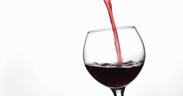 Růžové víno. Červené víno nalít do skleněného vína přes bílé pozadí