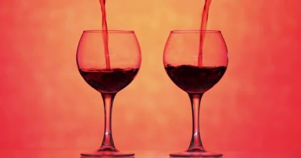 Růžové víno. Červené víno nalévat ve dvou skleničkách přes oranžové pozadí