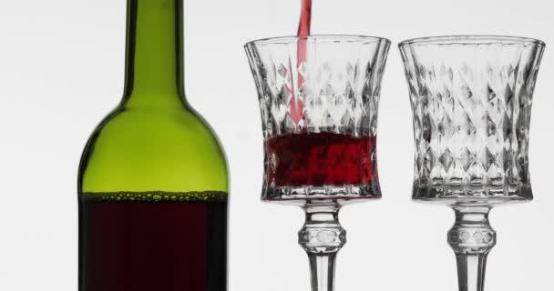 Rosenwein. Rotwein in zwei Weingläser auf weißem Hintergrund gießen