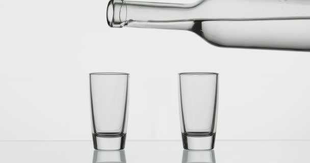 Vylil jsem dvě vodky z láhve do sklenice. Bílé pozadí