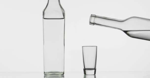 Nalil si vodku z láhve do sklenice. Bílé pozadí
