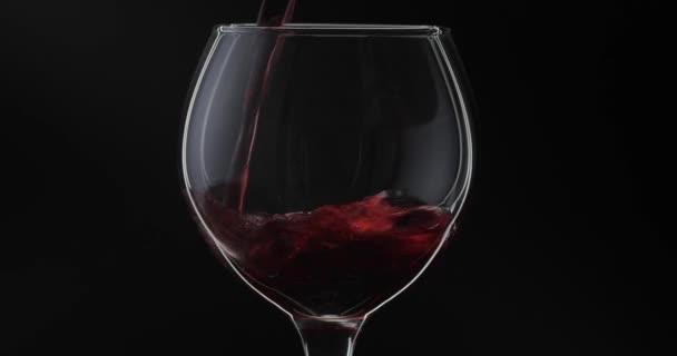 Růžové víno. Červené víno nalije do skleněného vína přes černé pozadí. Silueta