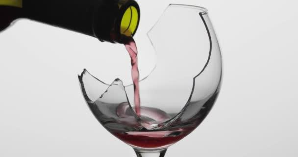 Víno. Červené víno nalévání v rozbité víno sklenice na bílém pozadí