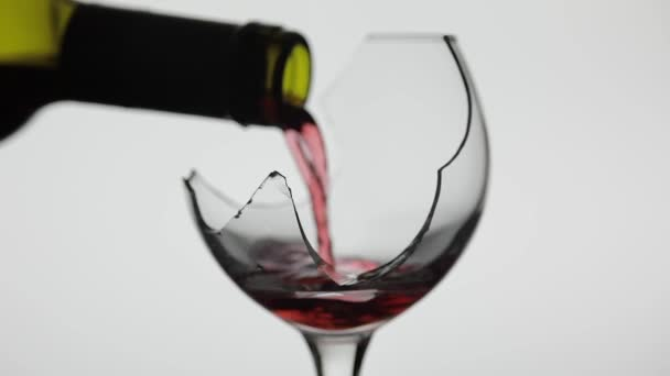 Wine. Red wine pouring in broken wine glass on the white background