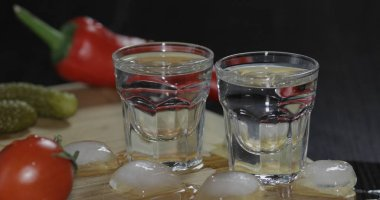 Two shots of vodka in glasses with ice cubes on the table with vegetables