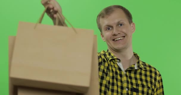 Young man on green screen chroma key background with shopping bags