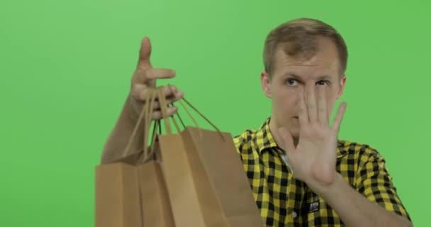 junger Mann auf grünem Bildschirm Chroma-Schlüsselhintergrund mit Einkaufstaschen