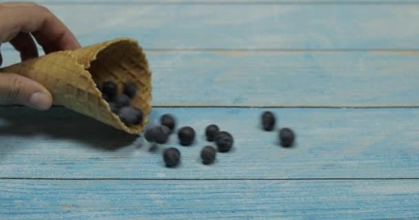 Zmrzlina. Bobule borůvky v vaflí na modrém dřevěném pozadí