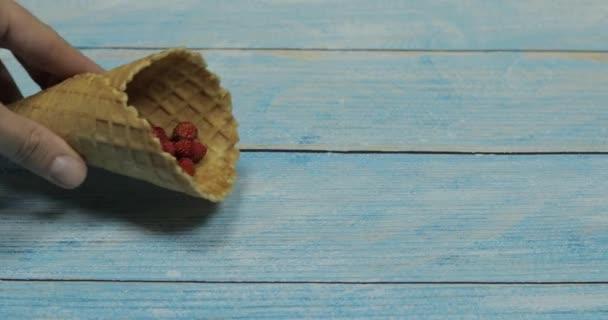 Zmrzlina. Jahodové bobule v vaflí na modrém dřevěném pozadí