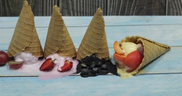 Sweet melted ice cream balls in a waffle cone. Different berries and fruits