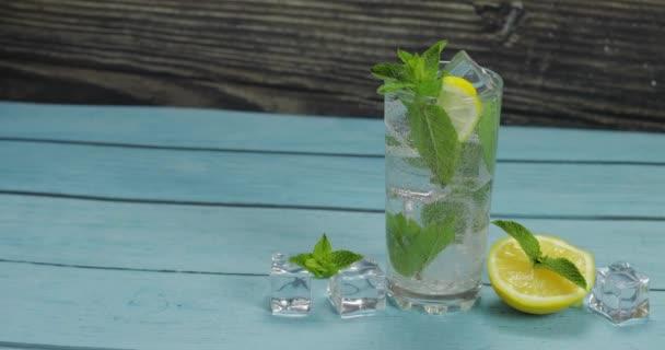 Átlátszó víz üvegben zöld mentalevél és jégkocka