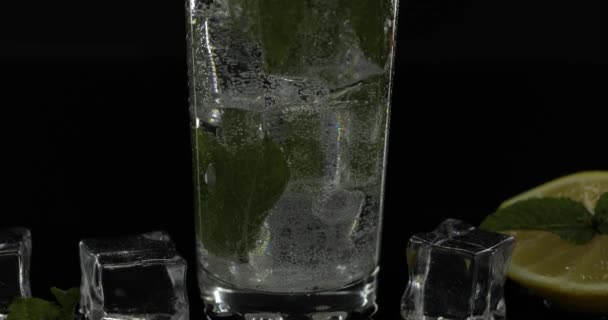 Clear water in glass with green mint leaves and ice cubes on black background