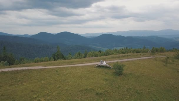Groom with bride together on a mountain hills. Aerial drone shot