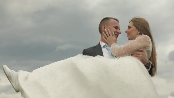 Ženich drží nevěstu v náručí na pozadí oblohy. Svatební pár. Šťastná rodina
