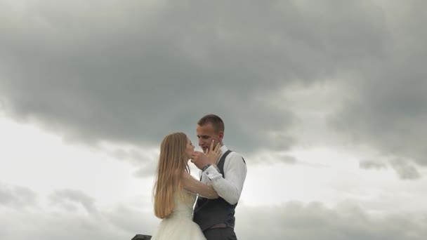 Ženich spolu s nevěstou na nebeském pozadí. Svatební pár. Šťastná rodina