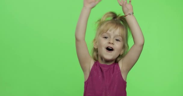 Girl child in purple dress waving with hands. Make faces and smile. Chroma Key