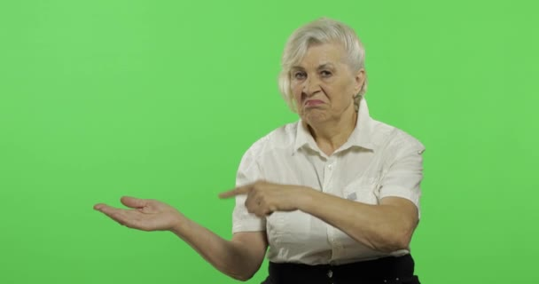 Starší žena ukazuje na něco a usmívá se. Stará babičko. Klíč Chroma