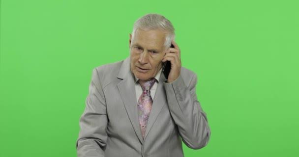 Jóképű idős üzletember beszél a smartphone. Öregember öltönyt