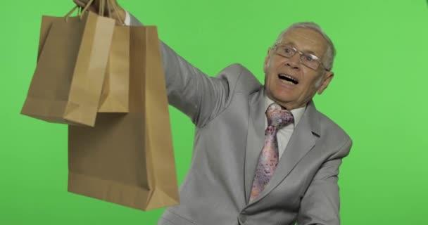 Boldog idős ember bevásárló táskák. Öregember a formális kopás után vásárlás