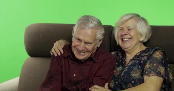 Senior idős férfi és nő ült össze egy kanapé és a tévénézés. chroma-kulcs