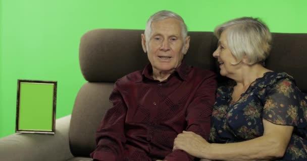 Senior idős férfi és nő ült együtt egy kanapé és beszélgetett. Chroma-kulcs
