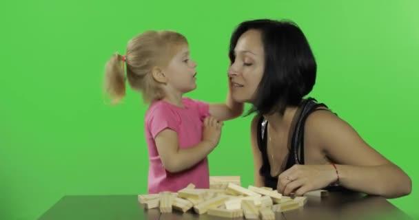Matka a dcera hrají na jengu. Dítě, které dělá z dřevěných bloků věž