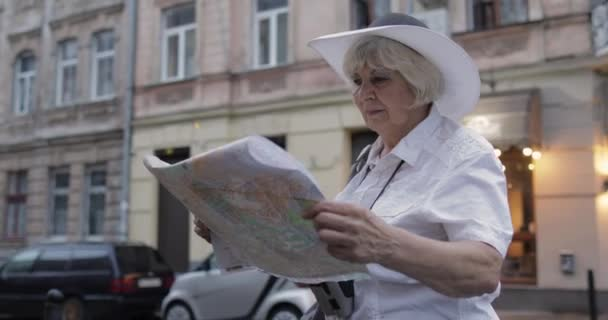 Senior female tourist exploring town with a map in hands. Looking for the route