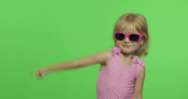 Dítě v růžových plavkách dělá sportovní cvičení, dívčí fitness trénink a tanec