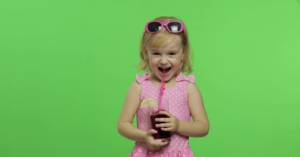 Dítě v růžovém obleku pije koktejl s pitnou slámou. Klíč Chroma