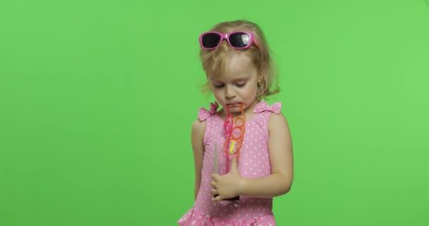 Gyermek rózsaszín fürdőruhát italok gyümölcslé koktél ivás szalma. Chroma-kulcs