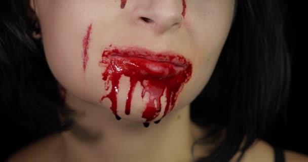 Blutiger Mund und Zähne des Mädchens. Vampir-Halloween-Make-up mit tropfendem Blut